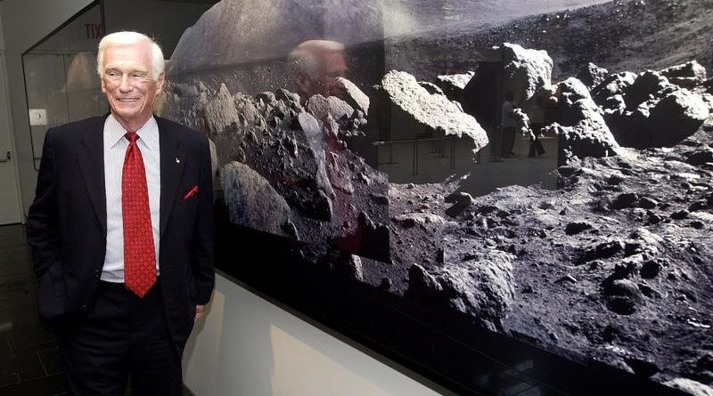 Former astronaut Gene Cernan, the last man to walk on the moon, stands next to a wall of photographs he made on the Apollo 17 mission, at the Museum of Natural History in New York, May 7, 2004.  REUTERS/Chip East  CME