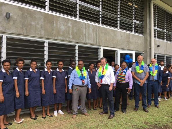 Delegates with students in front of the new academic building at the Lae